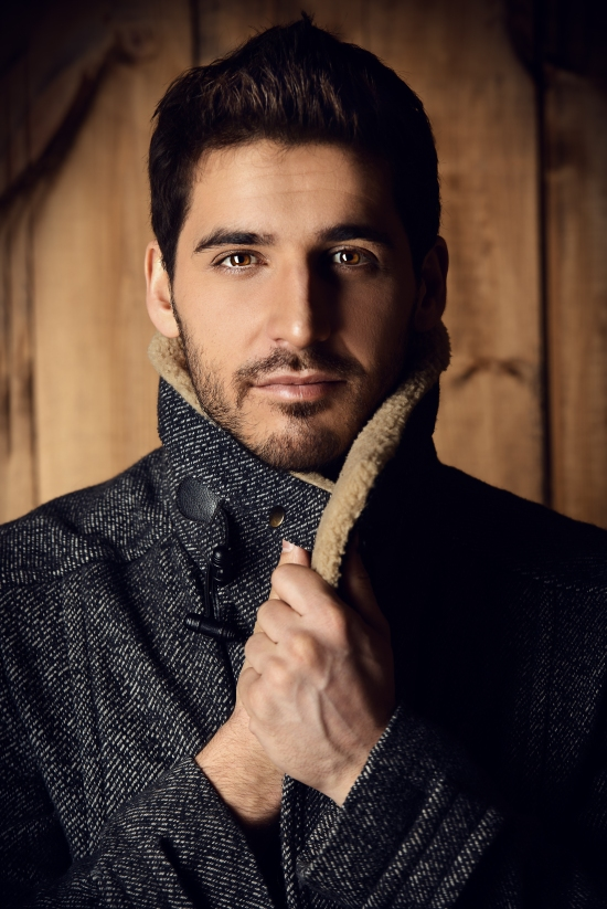 Vogue shot of a handsome male model in a coat standing by a wood